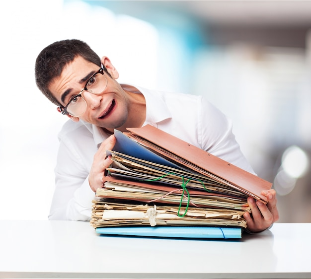 Stressed man looking at a mountain of folders
