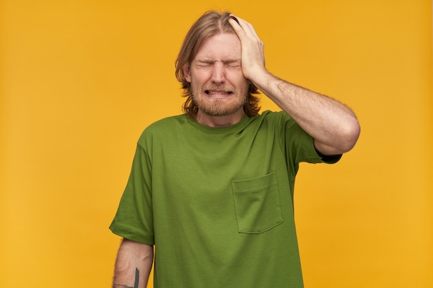 Stressed man, regretting guy with blond hair, beard and mustache. wearing green t-shirt. has tattoo. puts palm on his head. feels pain. stand isolated over yellow wall