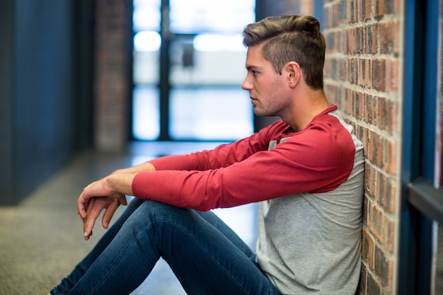 Stressed man sitting by wall