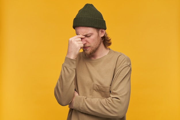 Uomo stressato, ragazzo stanco con capelli biondi, barba e baffi. indossare berretto verde e maglione beige. toccare il ponte del naso per il dolore. concentrandosi. stare isolato su una parete gialla