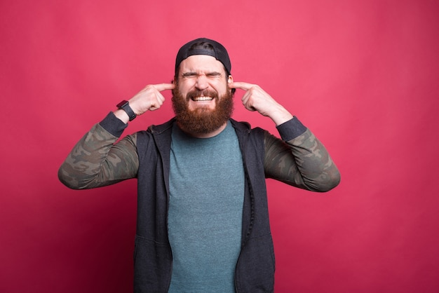 Stressed man with eyes closed is covering his ears over pink background.