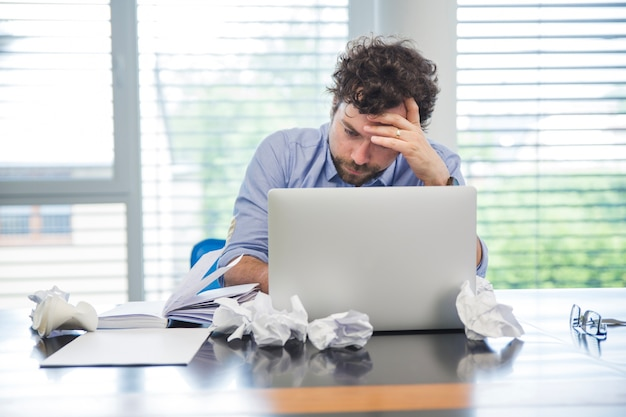 Подчеркнутый человек с ноутбуком в офисе