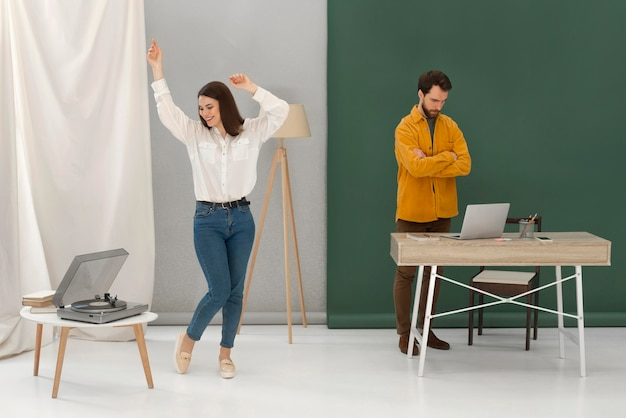 Stressed man working on laptop and woman dancing