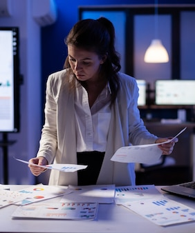 Stressed manager woman working with financial documents checking graphs, holding papers late at night