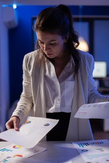 Stressed manager woman working with financial documents checking graphs