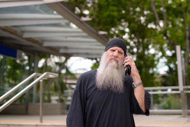 Stressed mature bearded hipster man talking on the phone outside the subway train station