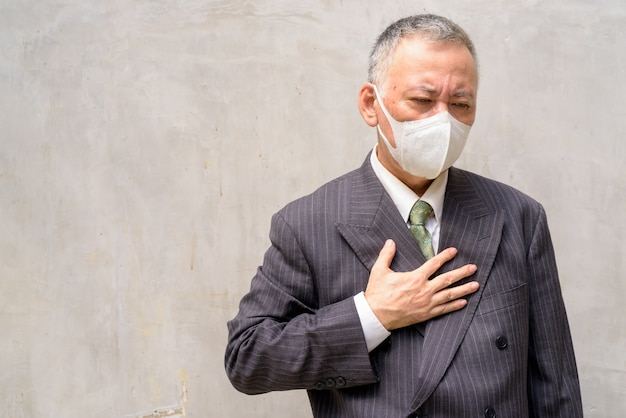 Stressed mature japanese businessman with mask coughing and getting sick outdoors