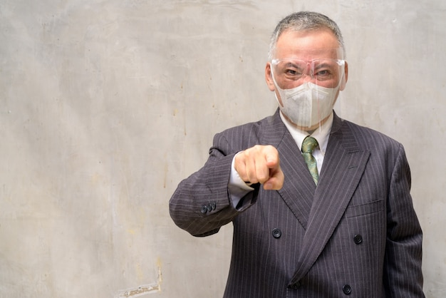 Stressed mature japanese businessman with mask and face shield pointing at camera