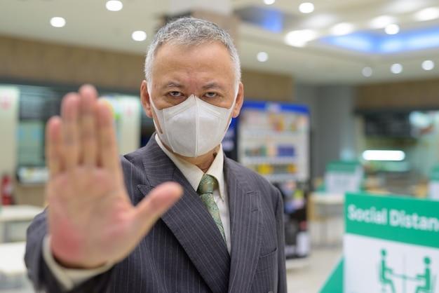 フードコートで停止ジェスチャーと社会的距離を示すマスクを持つ成熟した日本のビジネスマンを強調