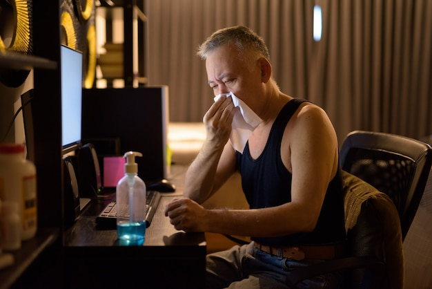 Stressed mature japanese man getting sick while working from home