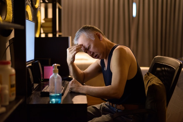 Stressed mature japanese man having headache while working from home