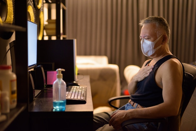 Stressed mature japanese man with mask getting sick while working overtime at home
