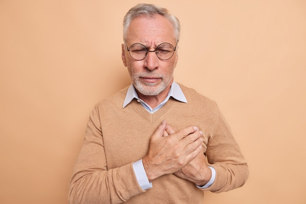 Stressed mature man touches chest suffers from heart attack