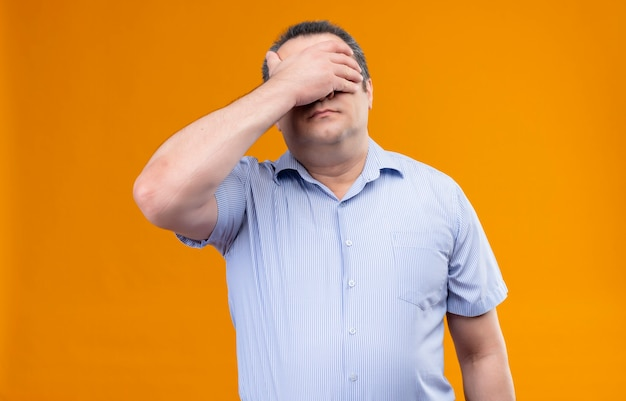 Stressed middle age man in blue striped shirt covering eyes with hands on an orange background