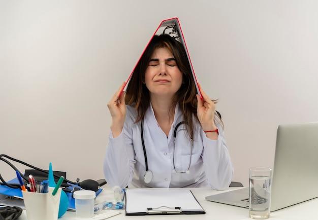 의료 가운과 청진기를 착용하고 의료 도구 클립 보드와 노트북이 고립 된 닫힌 눈 머리에 폴더를 들고 책상에 앉아 스트레스 중년 여성 의사