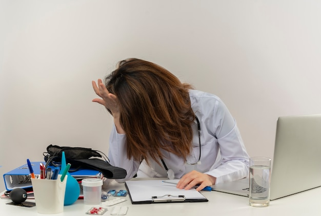 Stressed middle-aged female doctor wearing medical robe and stethoscope sitting at desk with medical tools clipboard and laptop putting hands on head and on desk isolated