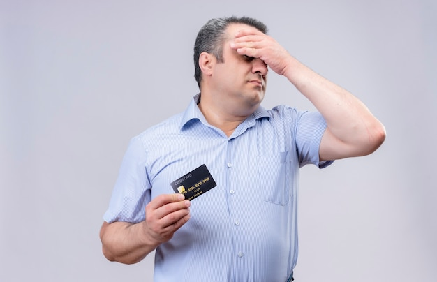 Stressed middle-aged man wearing blue striped shirt with hand on head showing credit card while standing on a white background