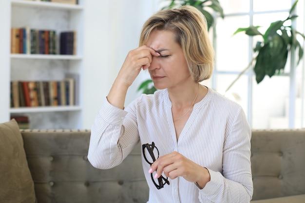 스트레스를 받는 중년 여성은 생각에 잠겨 거실 소파에 앉아 있습니다.