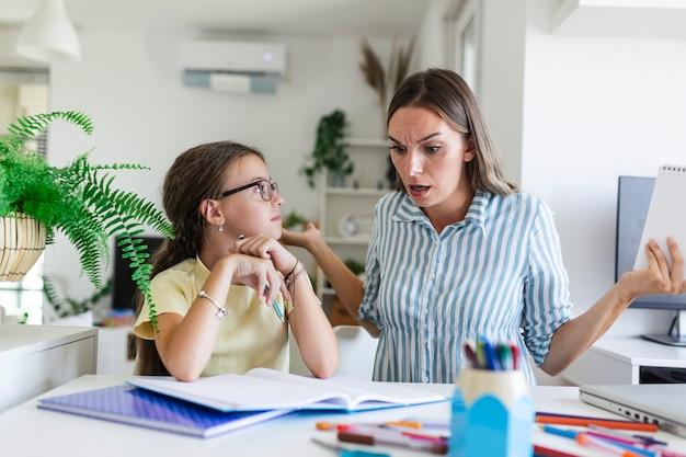 ストレスのたまった母と娘は、宿題の失敗、学校の問題の概念に不満を感じていました。母を見ている悲しい少女は、退屈な宿題をしたくない