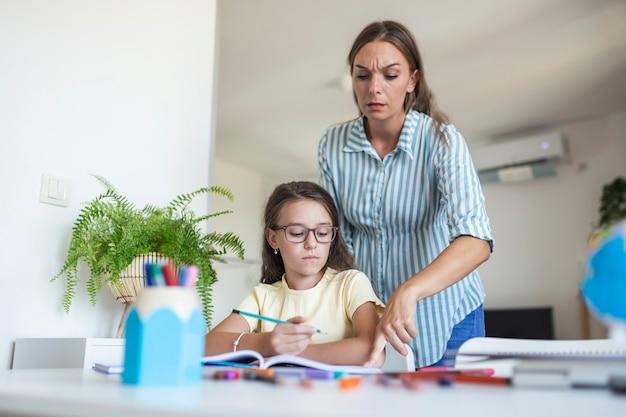 ストレスのたまった母と娘は、宿題の失敗、学校の問題の概念に不満を感じていました。悲しい少女は母親から背を向け、退屈な宿題をしたくない