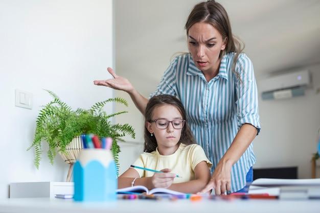 Подчеркнул мать и сын разочарованы из-за отказа от домашней работы, концепции школьных проблем. грустная девочка отвернулась от мамы, не хочет делать скучную домашнюю работу