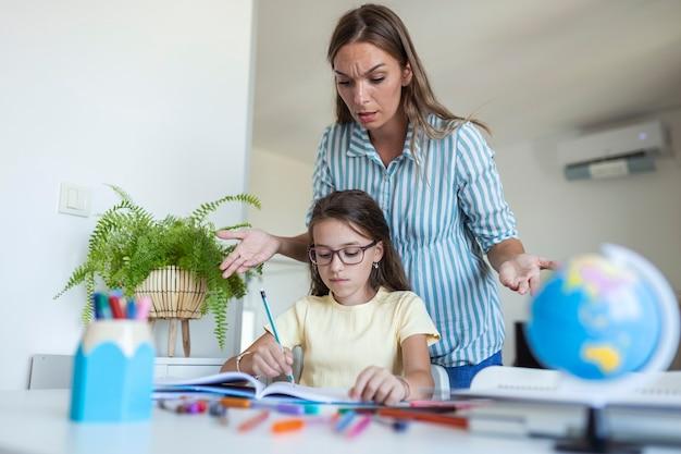 Подчеркнул мать и сын разочарованы из-за отказа от домашней работы, концепции школьных проблем. грустная маленькая девочка отвернулась от мамы, не хочет делать скучную домашнюю работу