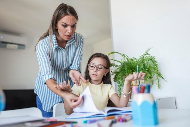ストレスのたまった母と息子は、宿題の失敗、学校の問題の概念に不満を感じていました。悲しい少女は母親から背を向け、退屈な宿題をしたくない