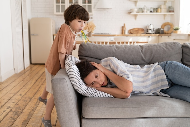 頑固な子供の息子の必死のソファに横たわっているストレスの多い母親は、子供の不正行為にうんざりしているお母さんを悩ませました