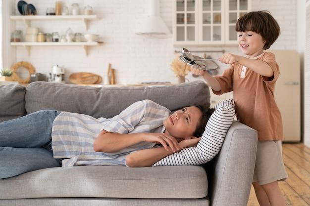 Подчеркнутая мать пытается спать на диване страдает от головной боли из-за того, что непослушный сын ударил металлическую посуду