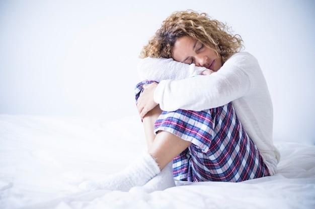 ストレスと保護は、白いベッドに座って膝を抱えて自分自身を保護し愛する若い白人女性を持つ人々を必要とするのを助けます-リラックスした女性の概念