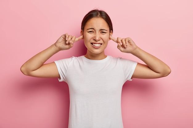 大きな音に悩まされているストレスのたまったアジアの女性、人差し指で耳を塞ぐ、悪い音を避ける、不満に眉をひそめる、黒い髪、白いtシャツを着ている、ピンクの壁にモデル