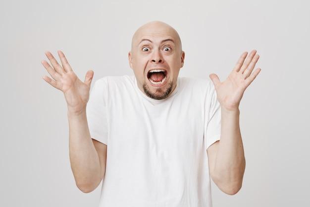 ストレスがたまったハゲのひげを生やした男が叫んで握手