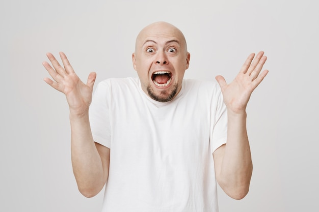Stressed-out bald bearded guy screaming and shaking hands