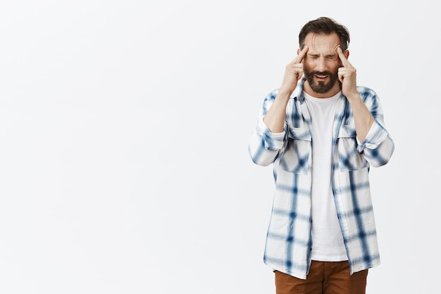 Stressed-out bearded mature man posing