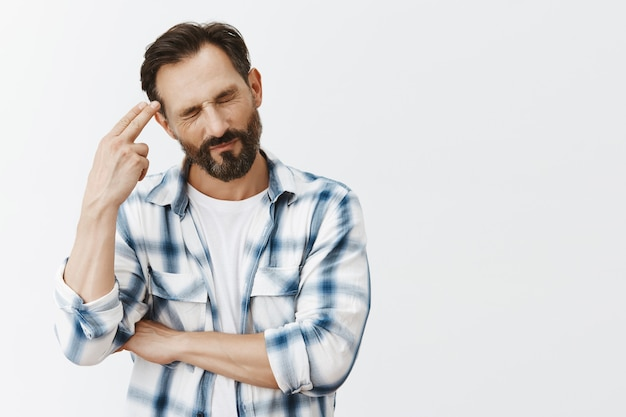 Stressed-out and tired bearded mature man posing