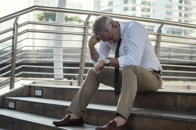 Stressed and overwhelmed senior businessman sit on stair outside office in downtown city