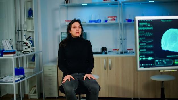 Paziente stressato seduto su una sedia nel laboratorio neurologico in attesa di un ricercatore medico che indaghi sulle funzioni cerebrali utilizzando strumenti ad alta tecnologia e neurologia