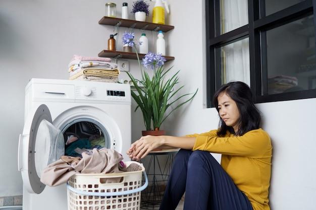 家で洗濯をしているかなりアジアの主婦を強調した