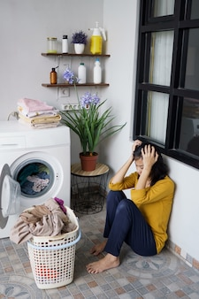 Stressed pretty asian housewife doing some laundry at home