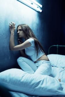 Подчеркнутая психо-женщина, сидящая в постели, бессонница, темная комната .. психоделическая женщина, имеющая проблемы каждую ночь, депрессия и стресс, грусть, психиатрическая больница