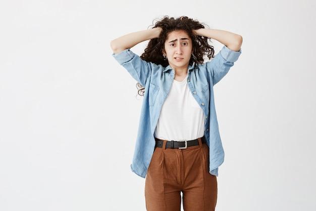 Подчеркнутая озадаченная юная небрежно одетая девушка с руками в темных волнистых волосах ощущает напряжение и стресс при столкновении с проблемами, не выдерживает давления, стискивая зубы. язык тела
