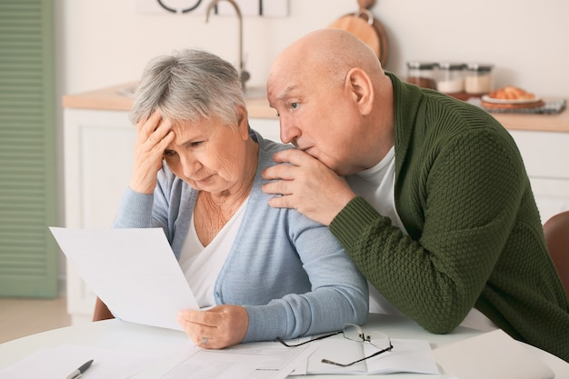 Stressed senior couple in debt at home