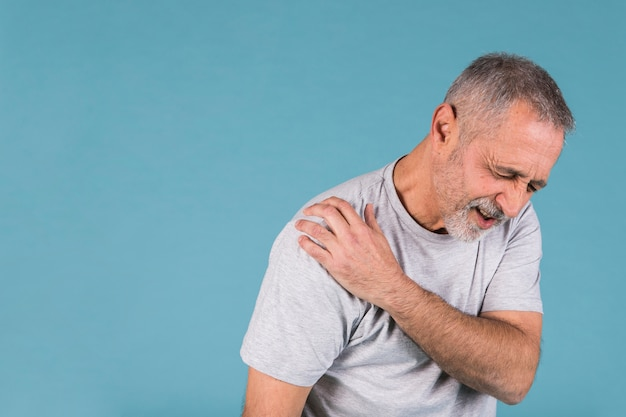 Stressed senior man with shoulder pain on blue backdrop