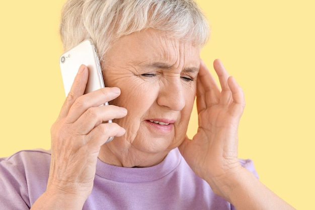 Stressed senior woman talking by phone on yellow