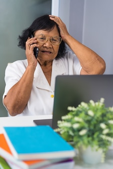 Stressed senior woman talking on mobile phone and working on laptop