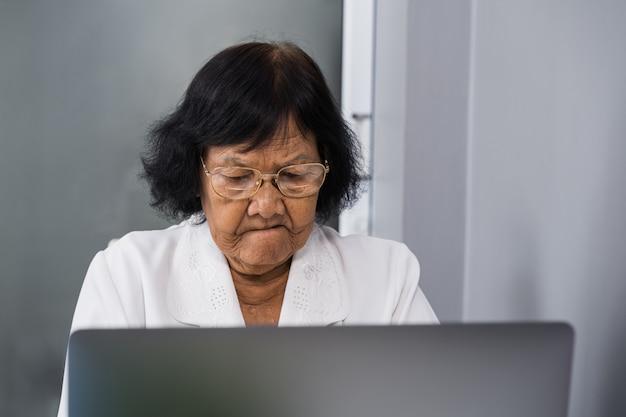 Stressed senior woman working on laptop computer