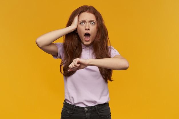 긴 생강 머리카락을 가진 스트레스를 받고 충격을받은 여성. 분홍색 티셔츠를 입고. 시간을 잊었다. 그녀의 머리를 만지고 손목 시계를 모방합니다. 오렌지 벽 위에 절연