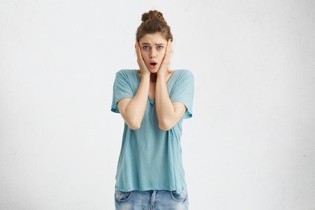 Подчеркнутая потрясенная молодая европейка с руками на щеках и открытым ртом удивлена неожиданной неприятной новостью, не может скрыть своих искренних эмоций