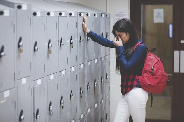 Stressed student beside her locker at the university