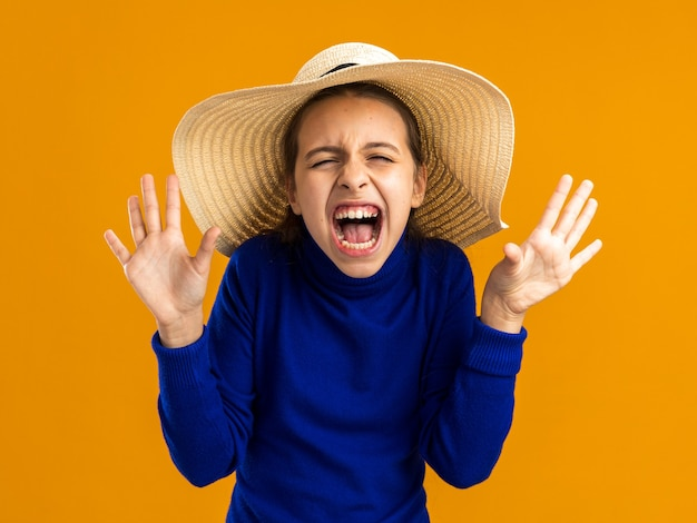 Adolescente stressato che indossa un cappello da spiaggia che mostra le mani vuote che urlano isolate sulla parete arancione